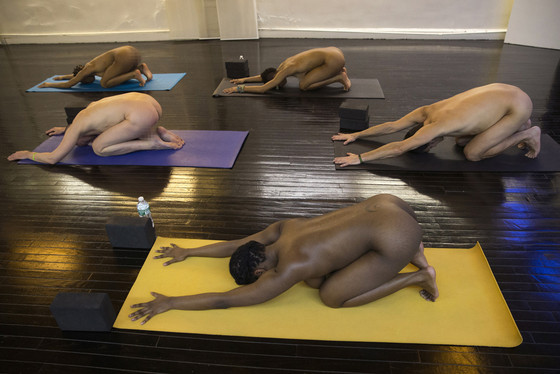 Participants in the Bold & Naked yoga class take positions during their session in New York